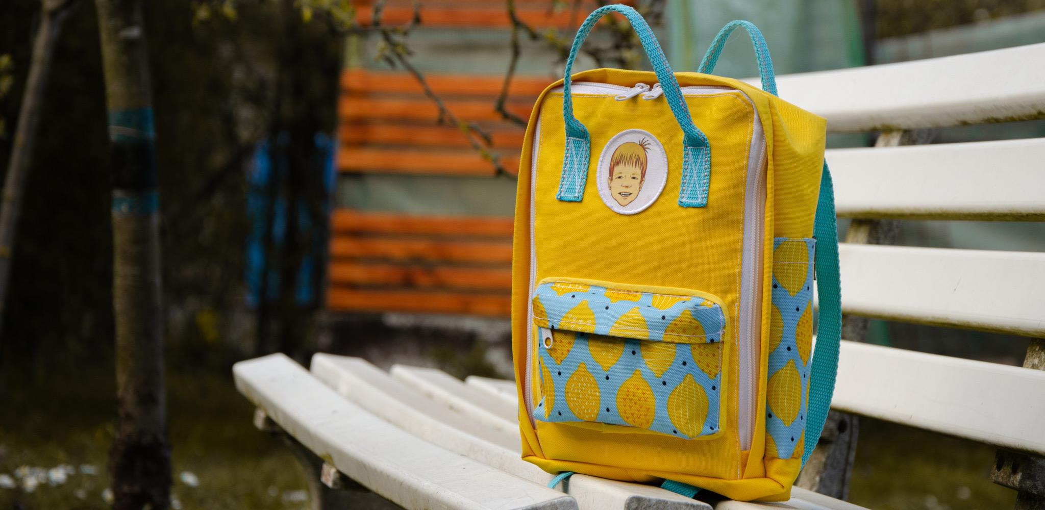 Gelber und Hellblauer Kinderrucksack mit Zitronenmuster, fotografiert auf einer alten Bank